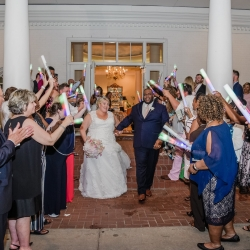 Bride and groom depart through a sea of glowsticks following their wedding reception at Providence Country Club