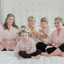 Bride and bridesmaids wear matching robes as they get ready for the big day with hair and makeup by Cali Stott Artistry