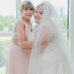 Bride smiles with her Matron of Honor as she prepares for her wedding day coordinated by Magnificent Moments Weddings