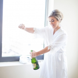 Bride pops some bubbly was she gets ready for her wedding coordinated by Magnificent Moments Weddings