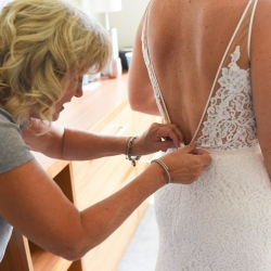 Brides mother helps with the final buttons as she gets ready for her wedding ceremony coordinated by Magnificent Moments Weddings