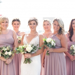 Bride poses with her bridesmaids among the Charlotte city skyline