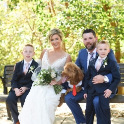Bride and groom pose with family during their fall wedding coordinated by Magnificent Moments Weddings