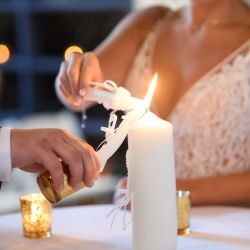 Bride and groom light their unity candle during their fall wedding ceremony coordinated by Magnificent Moments Weddings
