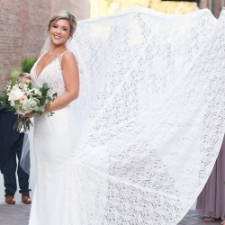 Bride shows of the stunning lace details of her wedding gown to Indigo Photography