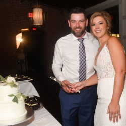 Bride and groom smile while cutting their cake created by Publix Baker