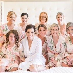 Bride poses with her bridesmaids as they get ready in matching robes for her spring wedding coordinated by Magnificent Moments Weddings