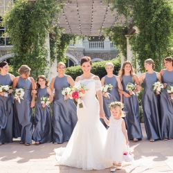 Bride poses with her bridesmaids wearing gray dresses and holding white bouquets before her wedding ceremony at The Ballantyne Hotel