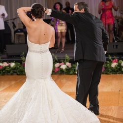 Groom spins his bride on the dance floor during their first dance coordinated by Magnificent Moments Weddings