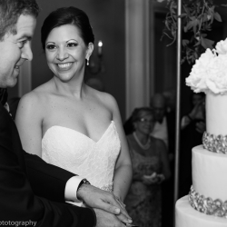 Bride smiles at her groom as they cut their Kathy Allen Cake topped with stunning sugar flowers