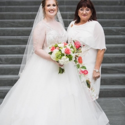 Bride smiles with her mother in Uptown Charlotte during her fall wedding coordinated by Magnificent Moments Weddings