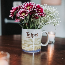 Travel theme coffee mugs served as floral vases during a travel themed wedding at Sugar Creek Brewery