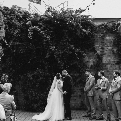 Bride and groom share a kiss and seal their vows during their wedding ceremony planned by Magnificent Moments Weddings
