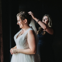 Bride puts on her veil as she prepares the final details to walk down the aisle to her wedding ceremony in Charlotte NC