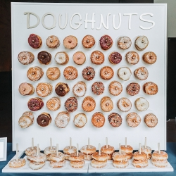 Custom Donut wall shows off sweet treats from Pepperbox Donuts during a fall wedding at Sugar Creek Brewery