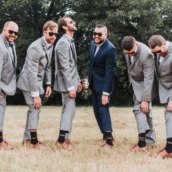 Groom and his groomsmen show off their custom socks to John Branch IV Photography