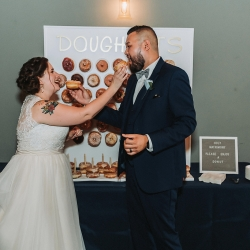 Bride and groom share a sweet treat from Pepperbox Donuts during their fall wedding reception coordinated by Magnificent Moments Weddings