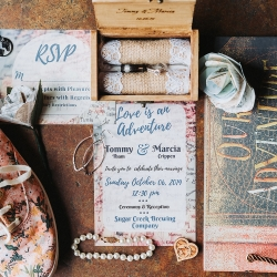Travel themed wedding details include a sweet guestbook and map themed invitations all captures by John Branch IV Photography