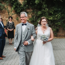 Bride is escorted down the aisle by her father during her fall wedding coordinated by Magnificent Moments Weddings
