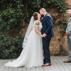 Bride and groom share a kiss as their seal their marriage during their fall wedding ceremony coordinated by Magnificent Moments Weddings