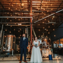 Bride and groom pose in Sugar Creek Brewery during their fall wedding captured by John IV Photography