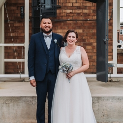 Bride and groom pose among the grounds of Sugar Creek Brewery during their fall wedding