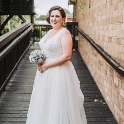 Bride poses holding her handmade bouquet made of map roses during her travel themed wedding coordinated by Magnificent Moments Weddings