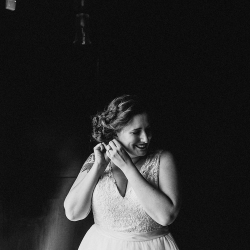Bride puts on her jewelry as she prepares to walk down the aisle during her fall wedding coordinated by Magnificent Moments Weddings