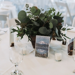 Lush greenery centerpieces created by Good Earth Flower Company are the perfect accents to a nature themed wedding at Triple C Barrel Room