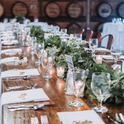 Lush greenery garland by Good Earth Flower Company perfectly accents a farmhouse head table for a nature themed wedding at Triple C Barrel Room