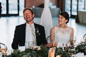 Bride and groom laugh as their friends and family toast them during their summer wedding coordinated by Magnificent Moments Weddings