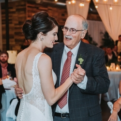 Bride shares a dance with her father coordinated by Magnificent Moments Weddings for a summer event at Triple C Barrel Room