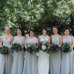 Bride poses with her bridesmaids wearing soft green dresses and holding lush greenery bouquets created by Good Earth Flower Company