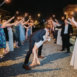 Groom dips his bride and captures one more kiss as they leave through a sea of sparklers coordinated by Magnificent Moments Weddings