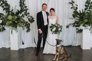 Bride and groom pose with their dog during their summer wedding at Tripe C Barrel Room