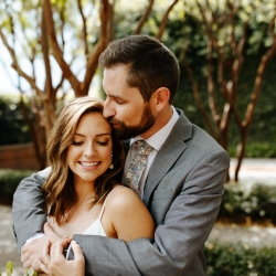 Groom kisses his bride as they prepare for their wedding coordinated by Magnificent Moments Weddings