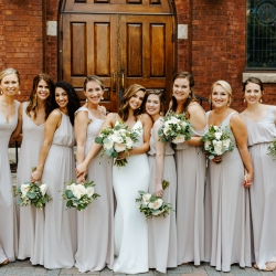 Bride poses with her bridesmaids in front of St Peter's Catholic Church before her wedding ceremony
