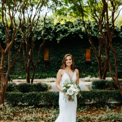 Bride poses among the trees of The Green in Uptown Charlotte during her wedding day coordinated by Magnificent Moments Weddings