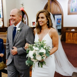Bride is escorted down the aisle by her father to her waiting groom during their fall wedding in Uptown Charlotte