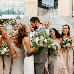 Bride and groom share a moment of laughter with their bridal party during their fall wedding at The Mint