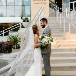 Bride and groom share a sweet moment before their wedding reception at The Mint Museum Uptown