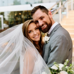 Bride and groom smile at the stairs of The Mint for Jordyn Schirrip Photography during their fall wedding