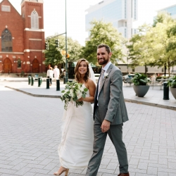 Bride and groom walk among the city streets of Charlotte during their Uptown Wedding