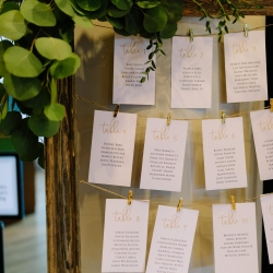 Table seating chart featured gold lettering and lush greenery for a fall wedding coordinated by Magnificent Moments Weddings