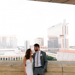 Bride and groom are capture amid the Charlotte skyline during their uptown wedding coordinated by Magnificent Moments Weddings