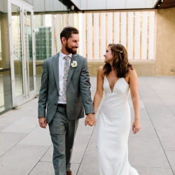 Bride and groom share a smile while walking hand in hand during their Uptown Charlotte Wedding
