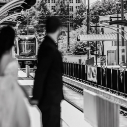 Bride and groom await the light rail as they prepare for their wedding at The Mint Museum Uptown