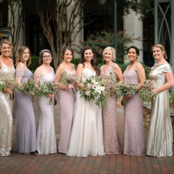 Bride poses with her bridesmaids wearing shades of purple at The Green for their summer wedding coordinated by Magnificent Moments Weddings