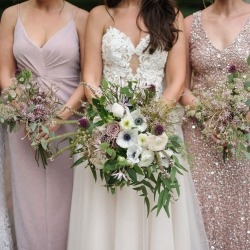 Bride poses with her bridesmaids all wearing stunning dresses and holding amazing bouquets created by Sarah Grimshaw Designs
