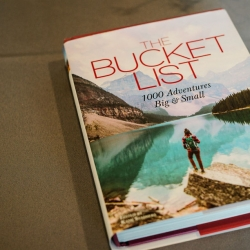 Fun book of bucket list adventures served as a guestbook for a summer wedding at The Mint Museum Uptown